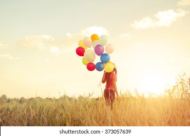 Happiness teen girl with colorful balloons enjoy in the sundown time at grassland. Happy birthday party. vintage color tone effect