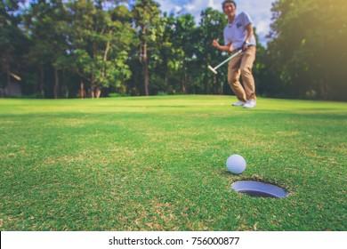 Happiness winner man golfer putting a golf ball in to hole. close up golf ball