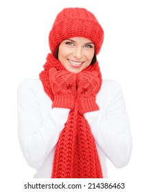 happiness, winter holidays, christmas and people concept - smiling young woman in red hat, scarf and mittens over white background