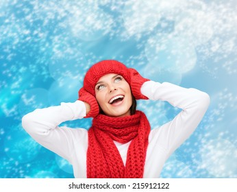 happiness, winter holidays, christmas and people concept - smiling young woman in red hat, scarf and mittens over blue snowy background