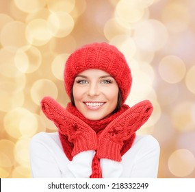 happiness, winter holidays, christmas and people concept - smiling young woman in red hat, scarf and mittens over beige lights background