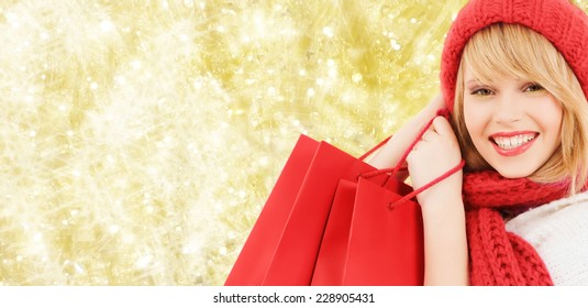 happiness, winter holidays, christmas and people concept - smiling young woman in hat and scarf with red shopping bags over yellow lights background