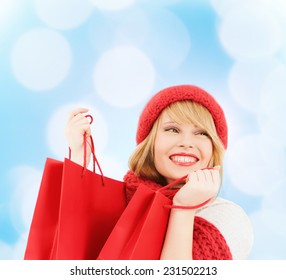 happiness, winter holidays, christmas and people concept - smiling young woman in hat and scarf with shopping bags over blue lights background
