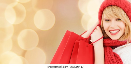 happiness, winter holidays, christmas and people concept - smiling young woman in hat and scarf with red shopping bags over beige lights background