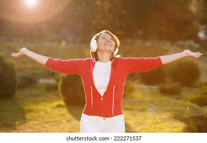 Happiness woman enjoy nature. Beauty girl on the street. The concept of freedom. Beauty girl under the sky and the sun's rays. Pleasure. Woman with headphones listening to music on her head.