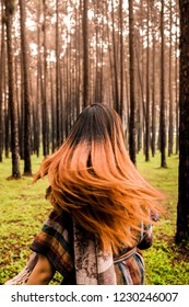 Happiness woman flicking her hair in a forest