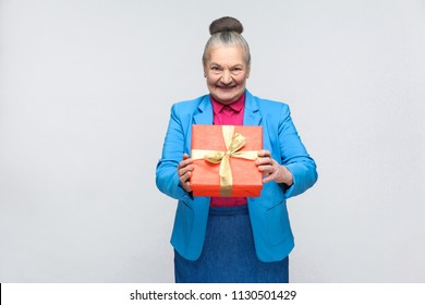 Happiness woman holding red gift box and toothy smiling. Portrait of handsome expressive grandmother in light blue suit with collected gray hair bun hairstyle. Studio shot, isolated on gray background