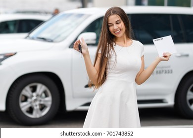 happiness woman with keys on background of car dealership