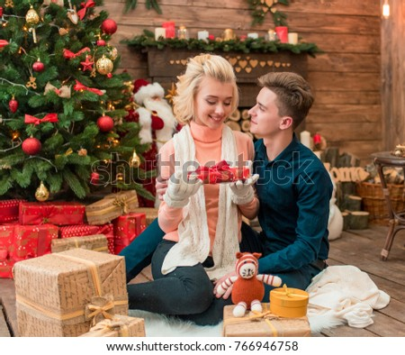 happiness young adult couple with gift boxes in a warm home atmosphere celebrating christmas young
