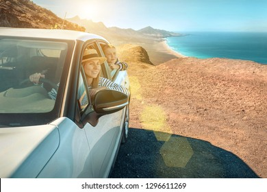 Happiness young woman in hat with her son sitting in white car and looking on beautiful ocean coastline view. Freedom, Family, Travell, Journej, Trip, Shooting concept.