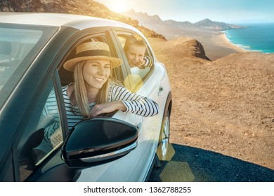 Happiness young woman in hat with her son sitting in white car and looking on beautiful ocean coastline view. Freedom, Family, Travel, Journey, Trip, Shooting concept.