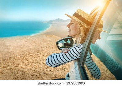 Happiness young woman in hat, sitting in her white car and looking on beautiful ocean coastline view with mountains. Traveler, Travel, Freedom concept.