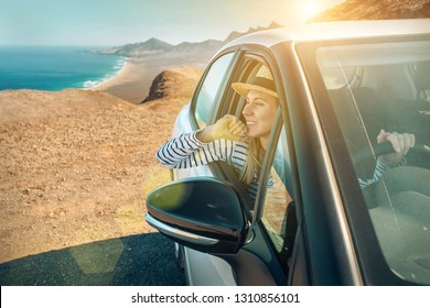 Happiness young woman traveler in hat, sitting in her white car and look on the beautiful ocean coastline and mountains. Travel, freedom, Trip, Journey concept.