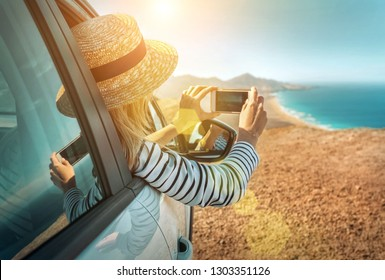 Happiness young woman traveler sitting in white car and shoot with her phone camera beautifull ocean coastline view. Freedom, Travell, Journej, Trip, Shooting concept.