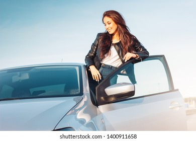Happpy beautiful charming brunette long hair young asian woman in black leather jacket in the car window