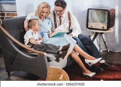 happy 1950s style family sitting on sofa and reading book together