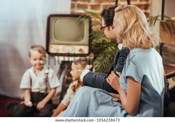 happy 1950s style parents sitting on sofa and lookign at cute little children playing at home