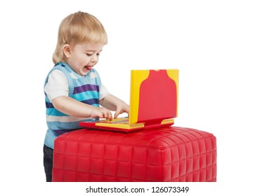 Happy 2 years child with computer. Young Technician. Small boy using a red and yellow laptop computer with his tongue out on white background. Studio shot