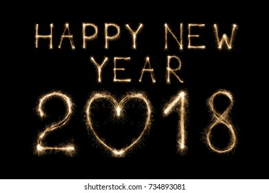 Happy 2018 new year written with sparkler fireworks on black background with heart shape, love symbol and greeting. Illuminated date figures for calendar