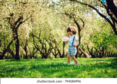 happy 3 years old child boy catching butterflies with net on the walk in sunny garden or park. Spring and summer outdoor activities, happy childhood concept.
