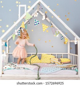 Happy 3 years old girl having fun in cute decorated house bed. Girl playing on bed in bedroom