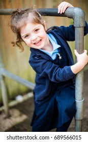 Happy 4 year old schoolgirl in school uniform smiles as she looks forward to starting school