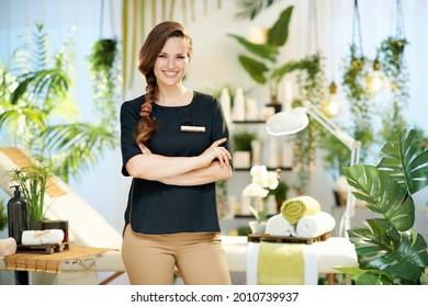happy 40 years old woman employee in modern beauty studio.