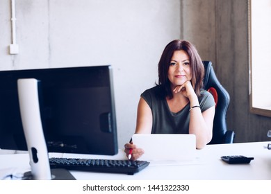 Happy 40s middle-aged brunette woman working in the office with computer