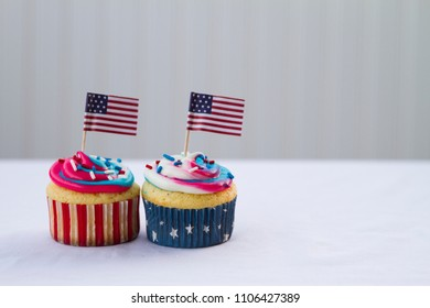 Happy 4th of July conceptual image with homemade blue red white color cupcakes and American flags on white background.