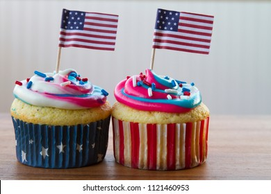 Happy 4th of July conceptual image with patriotic multicolored icing cupcakes and American flags.