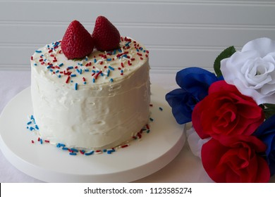 Happy 4th of July conceptual image with a homemade cake with patriotic decoration. With patriotic color flowers.