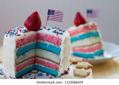 Happy 4th of July conceptual image with homemade cake of patriotic colored layers. With homemade star shaped cookies.
