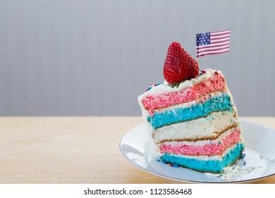 Happy 4th of July conceptual image with homemade cake of patriotic colored layers. White background with copy space.