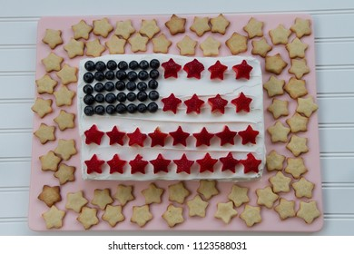 Happy 4th of July conceptual image with homemade cake that looks like American flag with many homemade star shaped cookies.