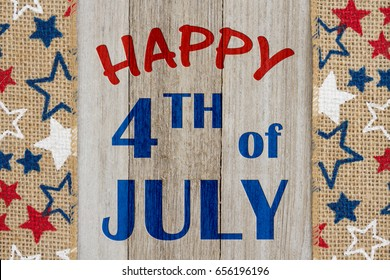 Happy 4th of July text with USA red, white and blue stars burlap ribbon on weathered wood