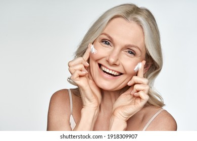 Happy 50s mid aged mature old blonde lady applying facial cream on face skin laughing enjoying anti age fresh soft skin care beauty spa treatment skincare creme isolated on white background. Portrait
