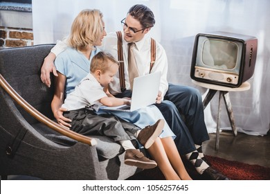 happy 50s style family with one child using laptop together at home