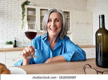 Happy 60s mature woman drinking wine video calling friend at home. Old middle aged lady holding glass talking to web cam by online social distance chat meeting sit at kitchen table. Webcam view.