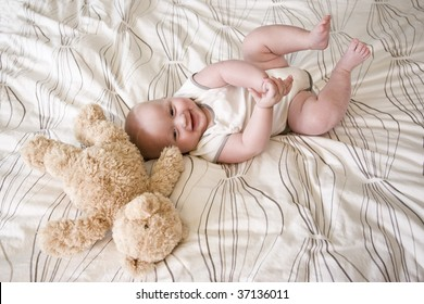 Happy 7 month old baby lying down next to teddy bear