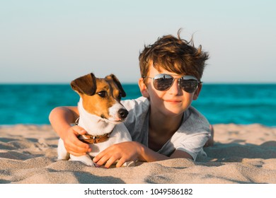 Happy 8 year old boy hugging his dog breed Jack russell at the seashore against a blue sky close up at sunset. Best friends rest and have fun on vacation. Home pet