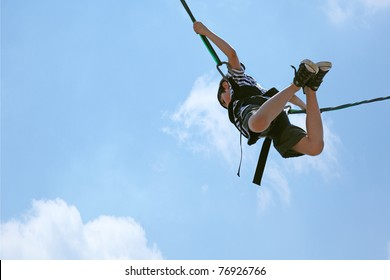 Happy 8 year old french-american boy bungee jumping against a blue and clouded sky with clipping path.