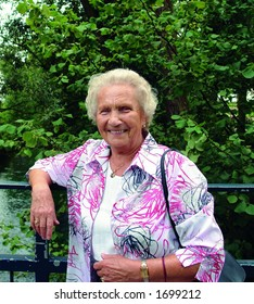 A happy 85 year old senior lady on a Sunday afternoon stroll in the park