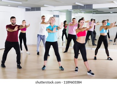 Happy active adults of different ages dancing at dance class