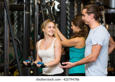 Happy active adults having strength training under coach control in gym