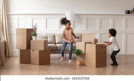 Happy active african american kids playing on moving day, two excited funny cute little mixed race children boy and girl running around cardboard boxes laughing in living room in new house apartment