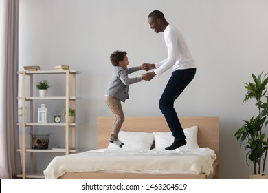 Happy active black father and cute small mixed race kid son holding hand jumping on bed mattress, carefree african american family dad with little child boy having fun laughing in bedroom together