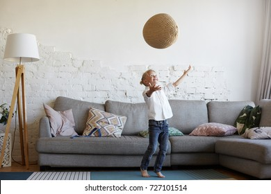 Happy active blonde little boy in white shirt and jeans standing at grey couch in modern home interior, playing with woven ball, throwing it in the air and then catching, having joyful cheerful smile