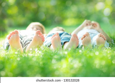 Happy active family lying on green grass in spring park. Healthy lifestyle concept