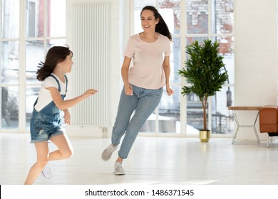 Happy active family mom nanny and cute small kid daughter playing tag and touch game at home, carefree mother baby sitter having fun with little child girl running laughing catching in living room