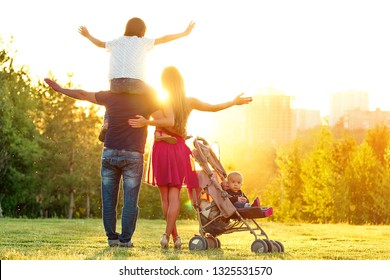 Happy active family photosession in the summer park. beautiful long-haired mother her husband with her daughter and son in a stroller rest on the nature green lawn . concept of freedom back view